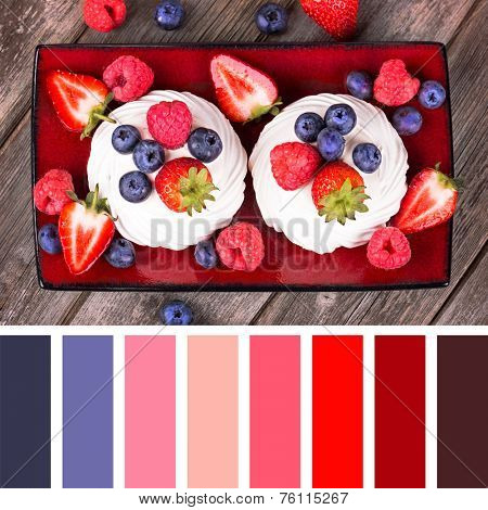 A platter of summer fruits in meringue nests, over old wood background, with a palette of complimentary colour swatches.