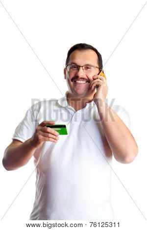 Mature Man Doing Some Telephone Banking And Giving The Bank His Debit Card Number