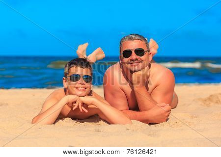 Happy Young Boy And Man On The Sea Beach