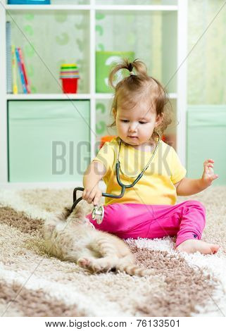 little kid girl plays doctor with kitten