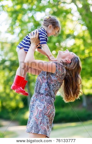 Beautiful Young Mother Holding Her Happy Little Kid Girl In Arms, Outdoors