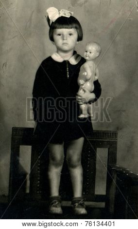 RUSSIA - CIRCA  1950s:  Vintage photo shows Portrait of little girl in school dress with bow.