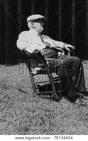 CANADA - CIRCA 1940s: Vintage photo shows elderly man sitting in a chair in the park.