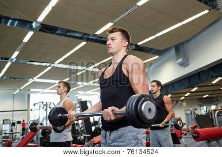 sport, bodybuilding, lifestyle and people concept - group of men with barbell flexing muscles in gym