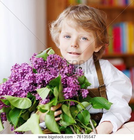 Adorable Smiling Little Boy With Blooming Purple Lilac Flowers