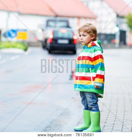 Happy Cute Little Boy Walking In City Through Rain