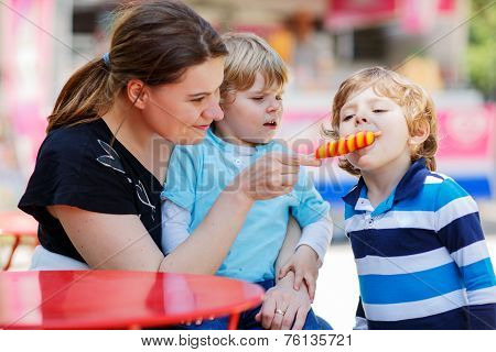 Mother Feeding Her Little Kid Boys With Ice Cream