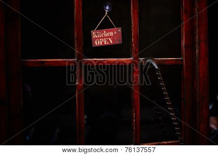 Antique wooden door of restaurant, open kitchen signboard on the door