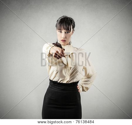 Serious businesswoman pointing out something into the camera