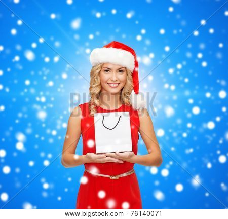 luxury, advertisement, holydays and sale concept - smiling woman in santa helper hat with white blank shopping bag over blue snowy background