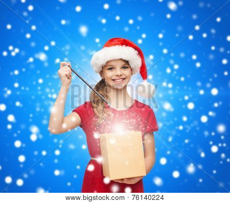 christmas, holidays, happiness and people concept - smiling girl in santa helper hat with gift box and magic wand over blue snowy background