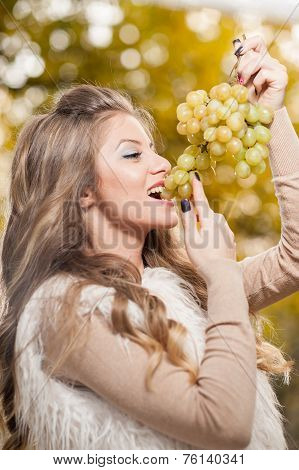 Young woman eating grapes outdoor. Sensual blonde female smiling holding a bunch of green grapes
