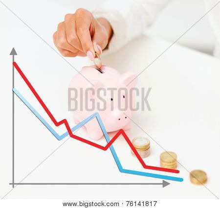 business, finances, crisis, people and money saving concept - close up of graph and female hand putting euro coins into piggy bank
