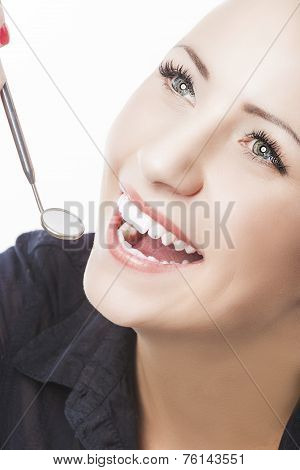 Examining Happy Female Patient's Teeth Using Mouth Dental Mirror.
