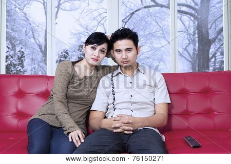 Bored Couple Watching Television At Home