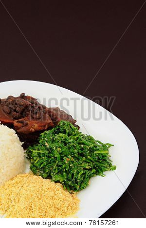 Brazilian Feijoada dish detail on brown background.