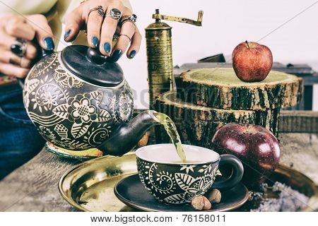 Pouring Tea From Teapot On Old Retro Wooden Table
