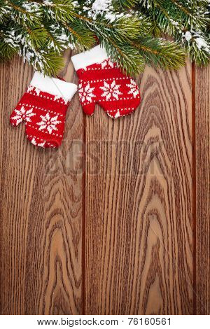 Christmas mitten decor and snow fir tree over wooden background with copy space