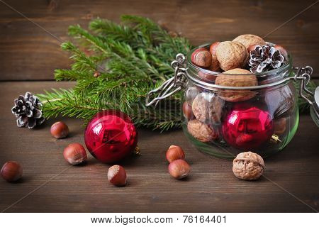 Christmas Concept (decoration). Jar  With Red Ball, Cone And Walnut  On Rustic Wooden Background