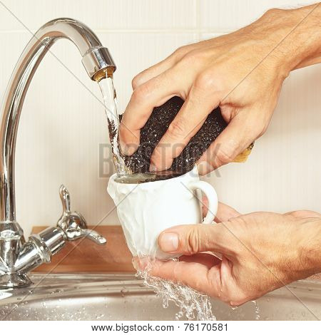 Hands with sponge wash the cup under running water in kitchen