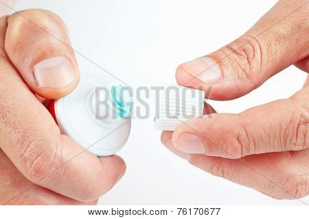 Hands holding opened tube of toothpaste on white background