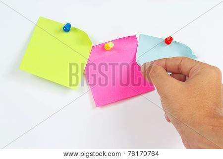 Hand tears off sticker from white message board
