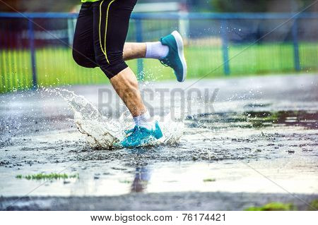 Detail of man running in rainy weather