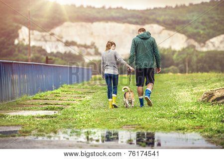 Young couple walk dog in rain