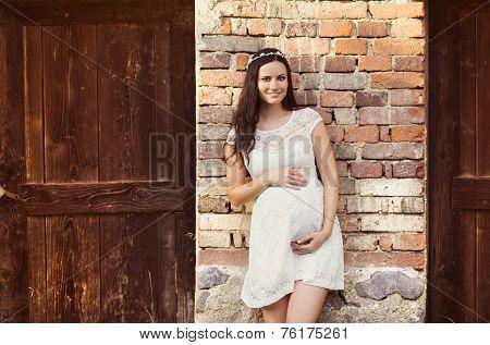 Pregnant woman against brick wall