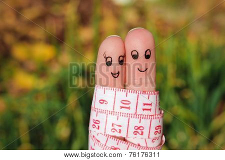 Finger art of a Happy couple with meter. The concept of losing weight together.