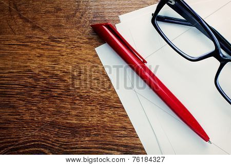 Pen And Reading Glasses On Blank Paper