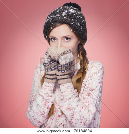 Beautiful redhair woman in winter outfit: warm sweater and hat with snow all over her. Isolated on p