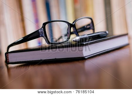 Close Up Glasses And Pen On Top Of The Book