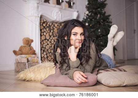 Beautiful Brunette Woman In Shorts And Sweater In New Year Decorated Interior With Christmas Tree In