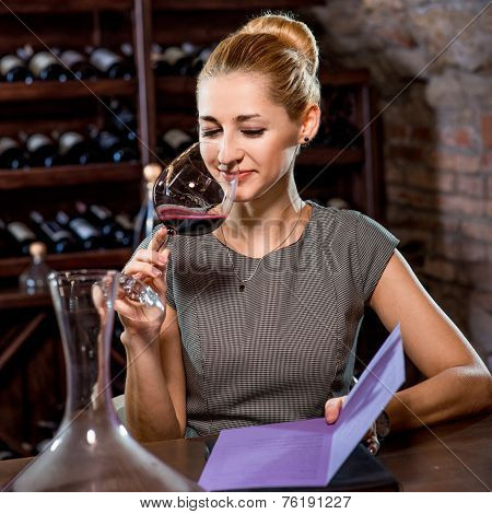 Woman tasting wine in the cellar