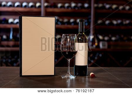 Wine bottle with glass and menu on the table