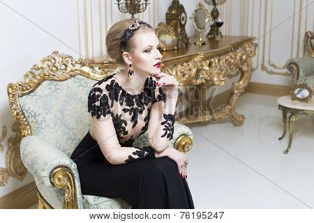 Beautiful blonde royal woman sitting on a bathtub with tulle on it in gorgeous luxury dress