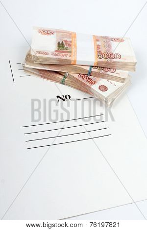 Vertical picture of packs of the ruble notes piled on the white folder