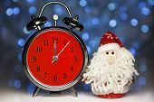 stock photo of father time  - Santa Claus or Father Frost and vintage alarm clock with red dial on christmas lights background - JPG