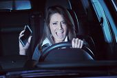 stock photo of terrifying  - Young terrified woman driving and having a car accident at night - JPG