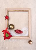 stock photo of glass-wool  - frame decorated with Christmas toys on beige wool fabric background - JPG