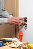 picture of electrician  - Electrician installing dimmer and a light switch - JPG