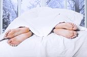 picture of intercourse  - Couple feet sleeping separately on the bedroom symbolizing couple having family problem - JPG