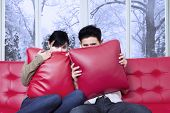 stock photo of horror  - Young couple sitting on sofa and hiding on the pillow when watching horror movie at home in winter day - JPG