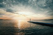 Постер, плакат: Woman With Arms Raised Standing On Pier At Sunset