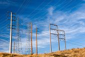stock photo of power transmission lines  - High voltage electrical  transmission power lines against late afternoon sky - JPG