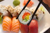 stock photo of chopsticks  - lunch with japaneese  sushi dish  with roll in chopsticks close up - JPG