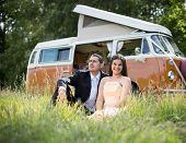 stock photo of camper-van  - Happy just married couple in an orange classic camper van parked outside in a green field ready for camping and a piknick - JPG