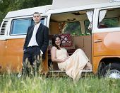 image of camper-van  - Happy just married couple in an orange classic camper van parked outside in a green field ready for camping and a piknick - JPG