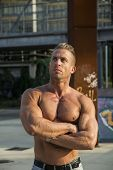 stock photo of hunk  - Handsome Muscular Shirtless Hunk Man Outdoor in City Setting - JPG